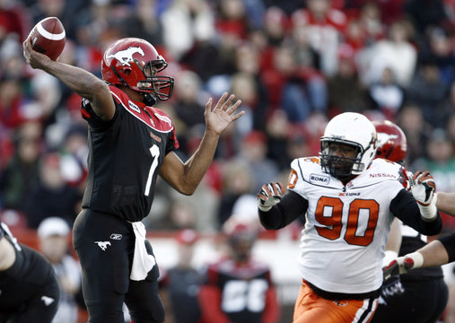 Calgary Stampeders quarterback Henry Burris throws a pass while being pressured by BC Lions Aaron Hunt during the first half of their CFL Western Final football game in Calgary