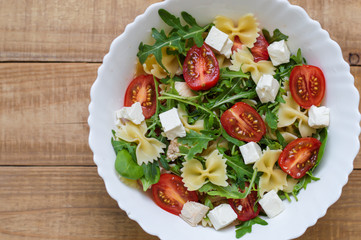 Homemade pasta salad with red cherry tomatoes, feta cheese, farfalle, arugula, baby spinach, chicken meat in white salad bowl on wooden table. Healthy diet