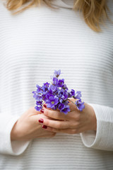 Closeup of woman's hands with small bunch of beautiful blue snowdrops. Spring mood. Girl with flowers.