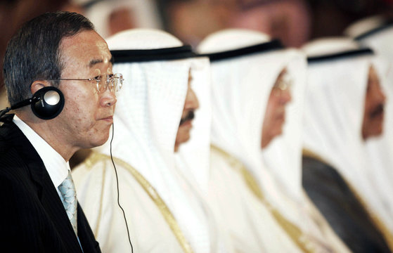 UN Secretary-General Ban listens to translation of a speech on his headphones at the UN Conference in Manama