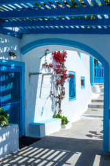 Greek Island Home with blue pergola and red flowers