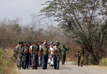 Venezuelan territorial guard volunteers get ready before exercise at a rural military base on the outskirts of Caracas