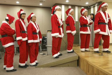 Volunteers wearing Santa Claus costume take part in a launching ceremony of Santa Claus Volunteers in Seoul