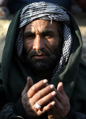 AN AFGHAN SUNI MUSLIM PRAYS DURING A HOLY PROCESSION IN KABUL.