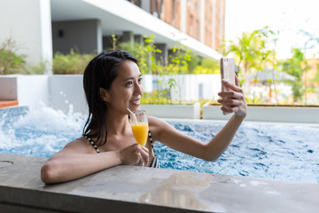 Young Woman with bikini enjoy in spa and taking selfie with cellphone
