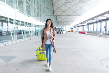 Woman go travel with her luggage and cellphone in airport