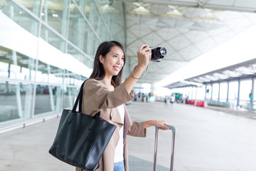 Woman taking photo with camera in airport