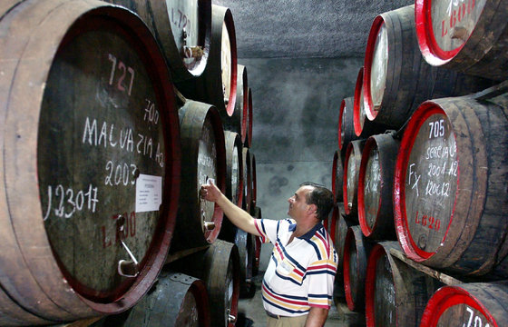 -PHOTO TAKEN 13OCT04- A worker knocks on a cask of maturing Madeira wine to check the level in the s..