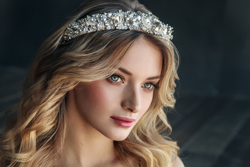 Fashion portrait of model with crown on the metal background