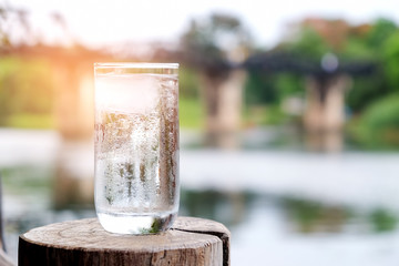 Glass of water put on wood with blurred steel bridge over the river.