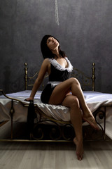 Beautiful sexy woman in maid costume sitting on a bed and poses