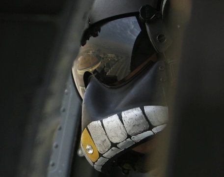 US military helicopter crewmember wears a face mask with skull design while flying on a mission in Baghdad