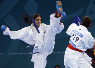 The Emirates' Sheikha Maitha Mohammed Rashed al-Makhtoum kicks at Kuwait's Abrar Abdulsayed in the over 65kg karate quarterfinal at the 15th Asian Games in Doha