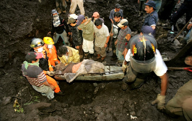 Guatemalan rescue workers recover body of a mudslide victim in Panabaj village