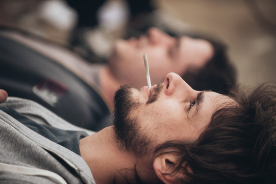 Two friends lying on the ground and smoke grass