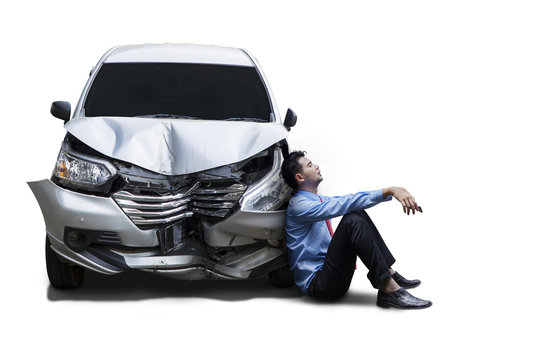 Frustrated businessman sits next to damaged car