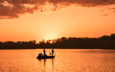 People are boating and fishing under sunset