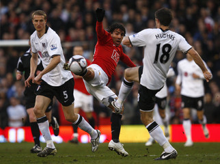 Fulham's Aaron Hughes challenges Manchester United's Carlos Tevez during their FA Cup quarter-final soccer match in London