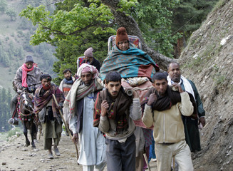 Kashmiri Muslim nomads carry Hindu pilgrims on palanquins and horses to the holy cave of Lord Shiva in Amarnath