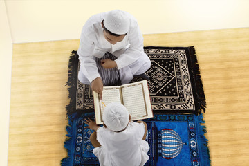 Little son and father reading Quran together