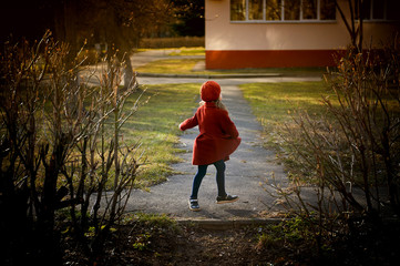 Baby 3 years with long hair. In a red beret and coat spinning in the street , in the rays of the sun. The state of happiness. Childhood