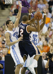 University of Virginia's Reynolds is stopped short of the basket by the University of North Carolina's Green and Noel