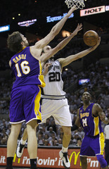 San Antonio Spurs Manu Ginobili  goes to the basket past  Los Angeles Lakers Pau Gasol as Kobe Bryant watches during Game 3 of their NBA Western Conference final basketball playoff series in San Antonio