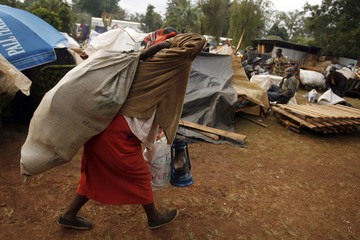 A woman from the Kikuyu tribe, who was displaced during post-election violence, carries her belongings outside a church in Kericho