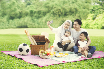 Muslim family with smartphone in the park
