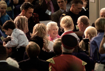 QUEEN LAUGHS WHILE CHATTING WITH PARTICIPANTS IN CULTURAL FAIR INTORONTO.