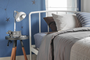 Beige and striped pillow on modern style bed setting and the blue wall