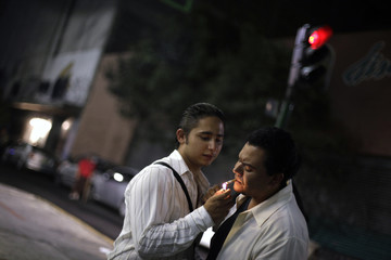 Sebastian A. Becerril lights the cigarette of his partner Rafael Ramirez in Mexico City