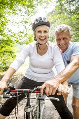 Mature woman on bike, Man assisting