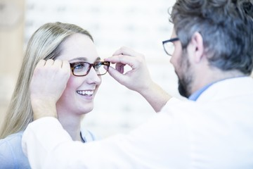 Optometrist trying glasses on woman