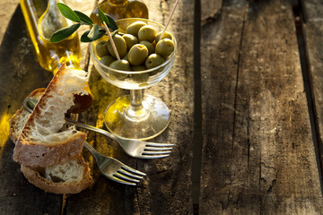 Glass glass filled with olives and bottles of olive oil on the rustic table