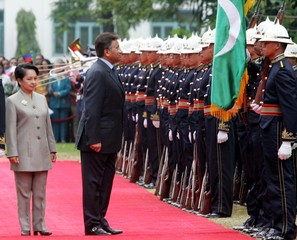 Visiting Pakistan President Musharraf pauses in front of his national flag in Manila.