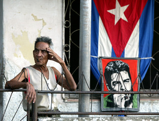 "A Cuban man smokes a cigar while standing next to a picture of late guerrilla leader Ernesto ""Che"" G.."