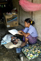 An Indian tsunami survivor reads a book beside a baby in a relief camp in remote Campbell Bay.