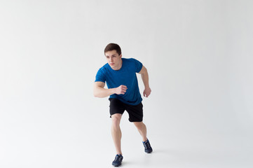 Running man on low start. Stands in rack, ready to achieve goals and wins. Young sexy Muscular male athlete wearing sporty blue t-shirt and shorts, studio portrait white background.Motivation concept