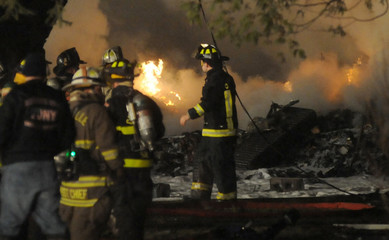 Firefighters are seen at the crash site of Continental Connection Flight 3407 operated by Colgan Air, which crashed in Clarence
