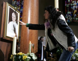 A mourner reaches out to touch a portrait of the late Pope John Paul II before a special mass ...