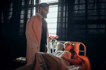 Man standing against ill woman in hospital bed