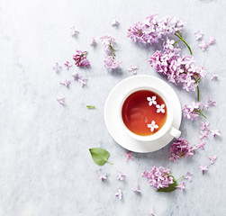 Cup of tea with lilac flowers on marble background