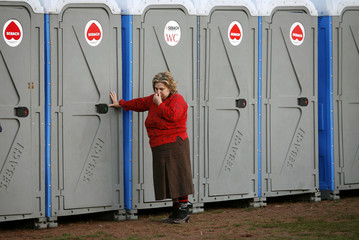 A woman leans on a temporary portable toilet at a camp where earthquake victims reside, in the Italian village of Paganica
