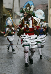 """Carnival revellers dressed as a """"Peliqueiros"""" run through a street in Spain's northwestern village of Laza"""
