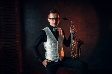 Male saxophonist posing with saxophone, jazz man