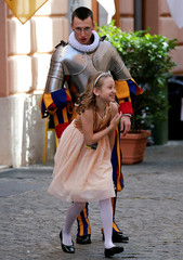 A new recruit of the Vatican's elite Swiss Guard plays with a girl before his swearing-in ceremony at the Vatican