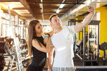 Young woman leaning on her boyfriend's shoulder while taking a selfie in gym.