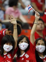 Liverpool fans wearing face masks cheer at Rajamangala national stadium during match between Liverpool and Thailand, in Bangkok
