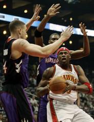 Atlanta Hawks Harrington is defended by Toronto Raptors Williams and Bosh in Atlanta.